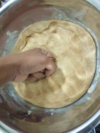 "After the first rise, the dough is ""punched"" down to release large bubbles of gas. This prepares the dough for shaping."
